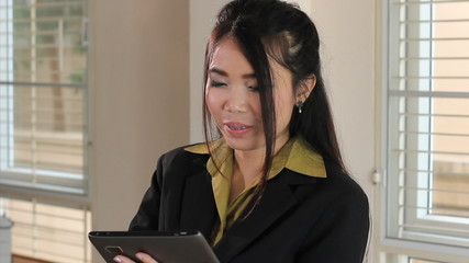 Cute Female Asian Office Worker Using Tablet