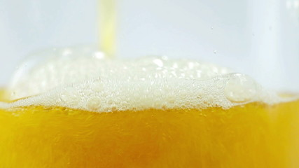 Beer beeing poured into translucent glass, white isolated backgr