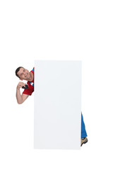 craftsman standing behind an ad board