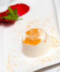 Italian dessert panna cotta on white plate decorated with coconu