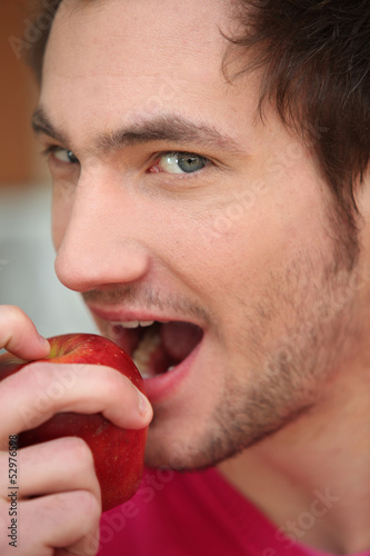 Young man biting into red apple