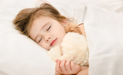 Adorable little girl sleeping in the bed