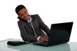Businessman typing whilst on telephone call