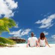 Happy couple sitting on the sunny beach