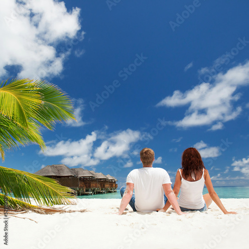 Happy couple sitting on the sunny beach