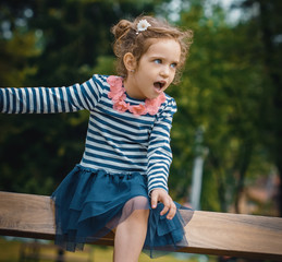 Playful little girl in park looking to side, outdoors
