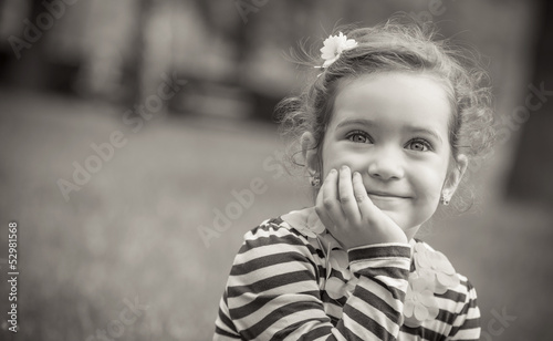 Black and white portrait of cute little girl in a park