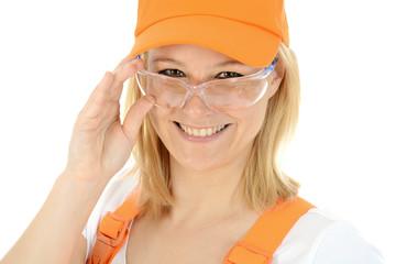 Freundliche Bauarbeiterin trägt Schutzbrille