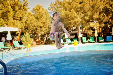 little boy jumping a hot summer day in a blue swimming pool