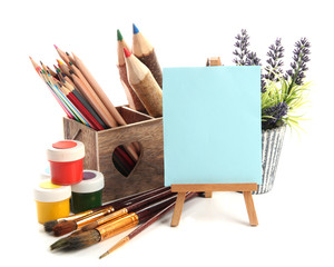 Pencils in wooden crate, paints, brushes and easel, isolated
