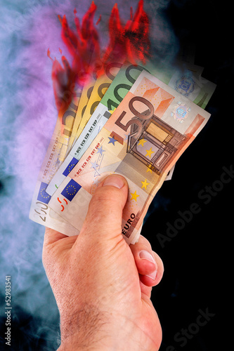 Hand with burning paper money