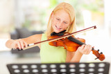 preteen girl practicing violin at home - 52986364