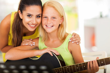 music tutor and preteen girl with a guitar