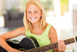 pre teen girl practicing guitar at home