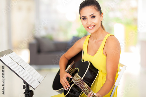 cute young woman practicing guitar