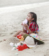 girl is playing with her toys on the beach