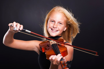 cheerful preteen girl playing violin
