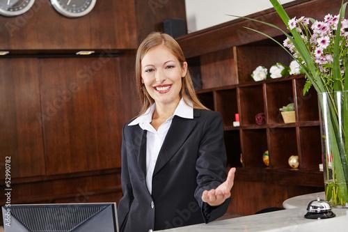 Empfangsdame begrüßt Gast im Hotel