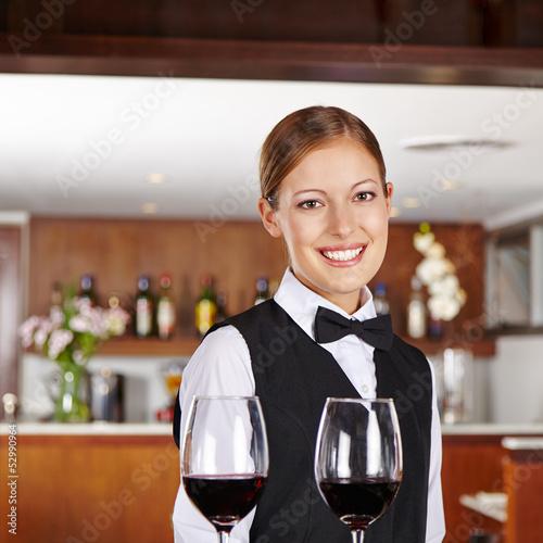 Kellnerin serviert Rotwein im Restaurant