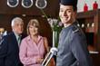 Lächelnder Concierge vor Seniorenpaar