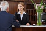 Rezeptionistin begrüßt Gast mit Handschlag