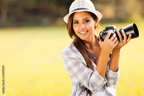 attractive young woman holding camera outdoors
