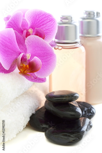 Cosmetics and towels with pink orchid.