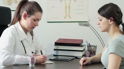 Female doctor writing rx prescription for patient