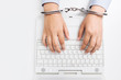 Female hands in handcuffs, with laptop