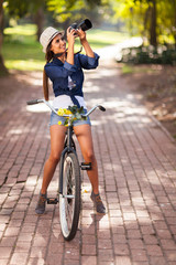 attractive young woman taking pictures on her bike
