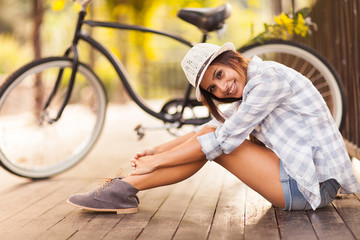 young woman sitting next to her bike outdoors