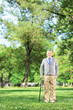Full length portrait of a senior man walking with a cane in park