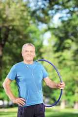 Fit mature man holding a hulahoop in a park