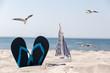 canvas print picture - Schuhe und Schiff im Sand umringt von Möwen