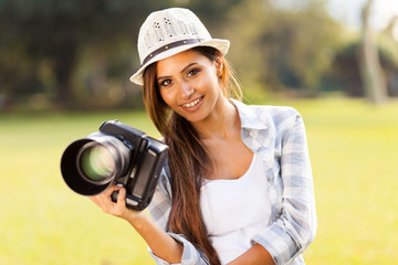 attractive girl holding camera outdoors