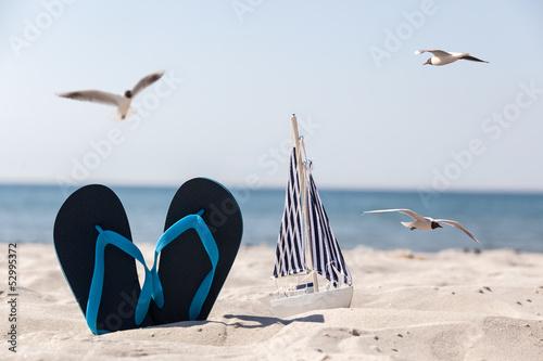 canvas print picture Schuhe und Schiff im Sand umringt von Möwen