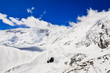 Snow mountain peak with clouds and blue sky