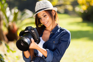 young female photographer checking pictures on camera