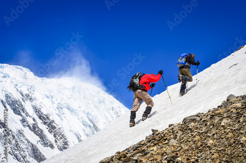 Two mountain trekkers on snow with peaks background