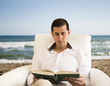 relaxed man reading a book and drinking on the beach