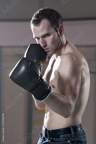Waist-up of young male boxer in gym