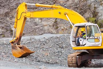 road construction worker operating excavator