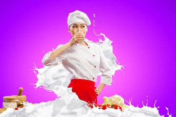 Asian female cook against milk splashes