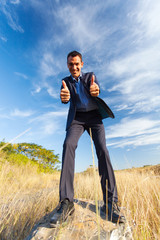 businessman on top of rock giving thumbs up