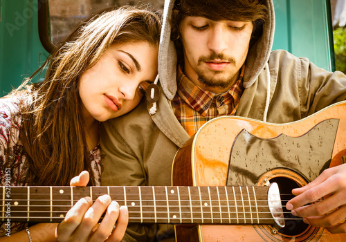 Romantic young Couple playing Guitar outdoor after the Rain