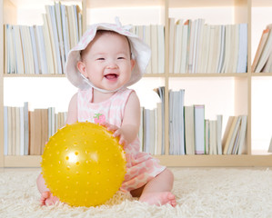 Lovely baby girl playing with ball