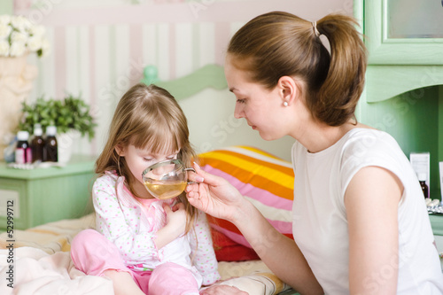 mother gives to drink to the sick child