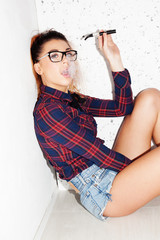 Girl with nerdy look sitting on the ground smoking e-cig