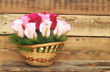 Paper flower in a basket over wooden background. Love concept