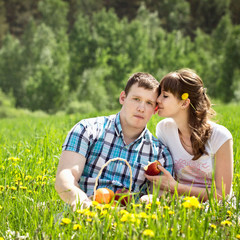 Loving couple with a basket of fruit in the field